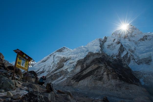 Trekker usar celular inteligente tirando foto da montanha do everest com everest acampamento base sig Foto Premium