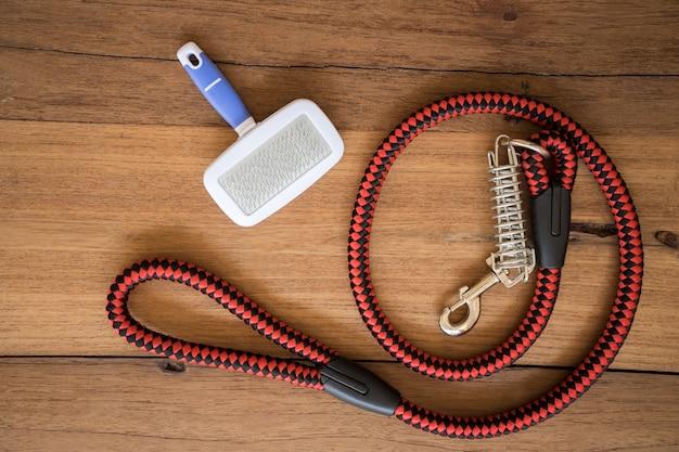Trelas e escova do animal de estimação no fundo de madeira. Foto Premium
