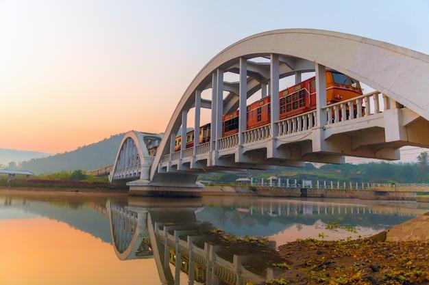 Trem diesel passando a ponte ferroviária branca durante o nascer do sol da manhã. Foto Premium