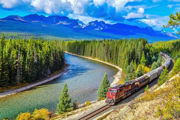 Trem passando a famosa curva de morant em bow valley no outono Foto Premium