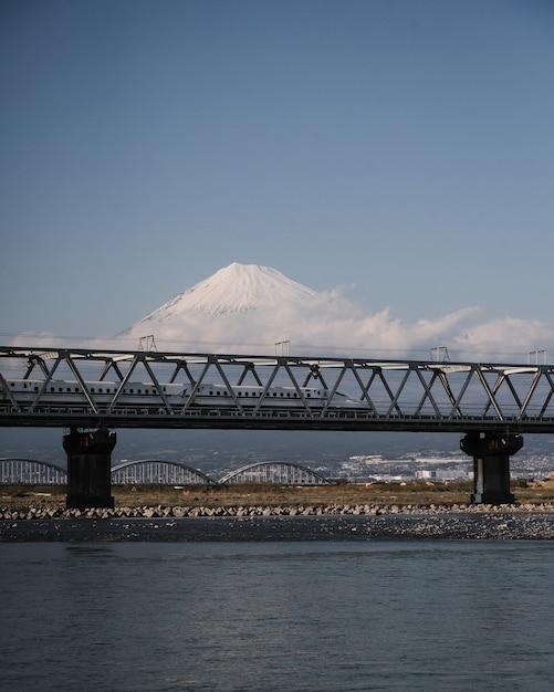 Trem shinkansen de alta velocidade sobre o rio fuji com uma montanha fuji fascinante Foto gratuita