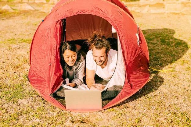 Trendy, par, mentindo, em, barraca, com, laptop Foto gratuita