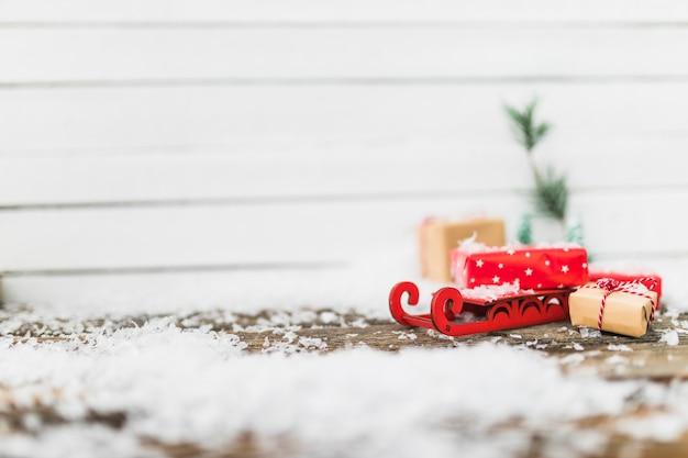 Trenó de brinquedo perto de caixas de presente entre flocos de neve Foto gratuita
