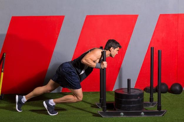 Trenó empurrar homem empurrando pesos treino exercício Foto Premium