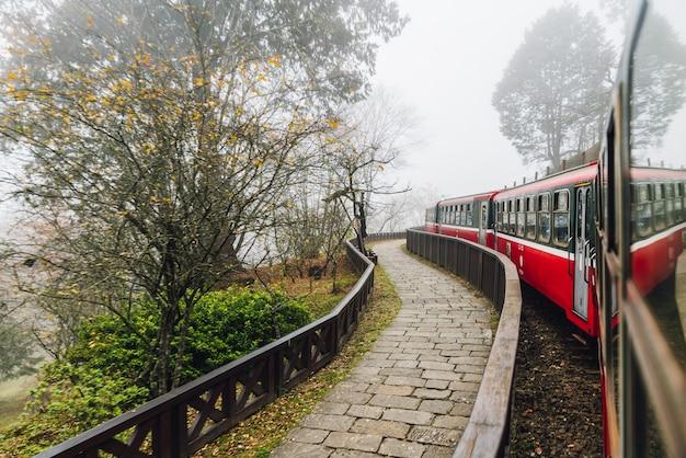 Trens vermelhos moventes na parada de alishan forest railway com as árvores do borrão de movimento fora em alishan, taiwan. Foto Premium