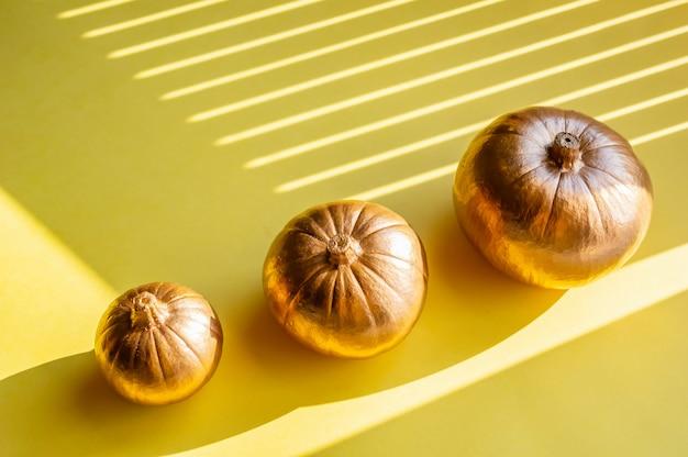 Três abóboras decorativas douradas sobre um fundo amarelo Foto Premium