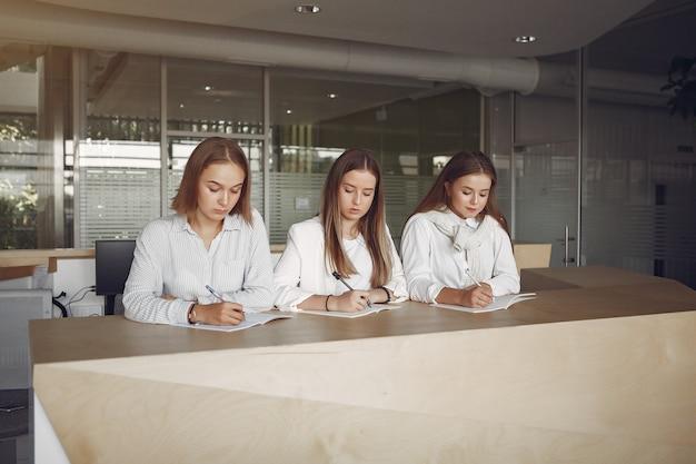Três alunos sentados à mesa na sala de aula Foto gratuita