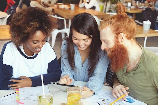 Três alunos trabalhando juntos em tarefas caseiras, sentados em um café, fazendo pesquisas, navegando na internet, usando wi-fi no touch pad. Foto gratuita
