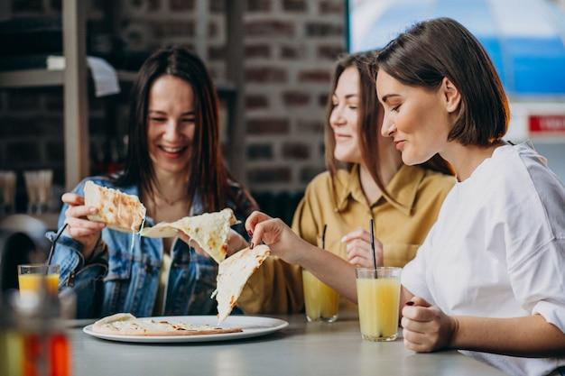 Três amigas comendo pizza em um bar Foto gratuita