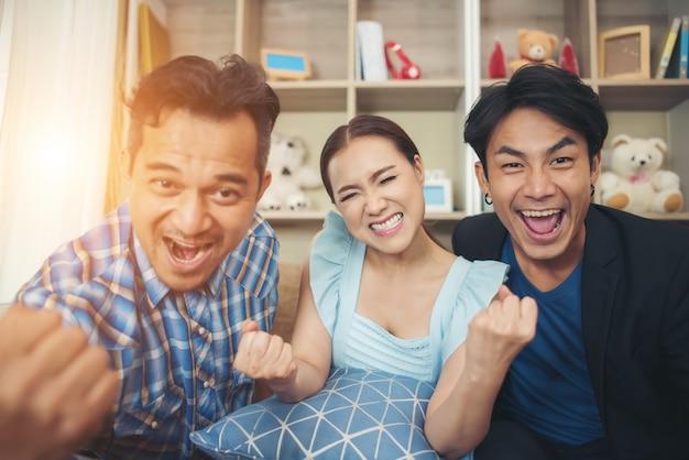Três amigos estão felizes por assistir tv Foto gratuita