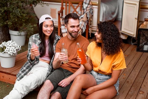 Três amigos felizes bebendo ao ar livre Foto gratuita