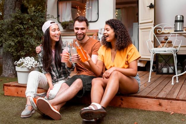 Três amigos felizes bebendo e sorrindo Foto gratuita