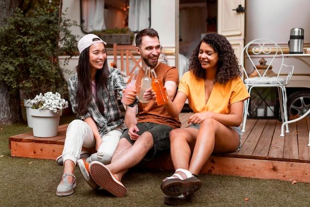 Três amigos felizes sentados e compartilhando bebidas Foto gratuita