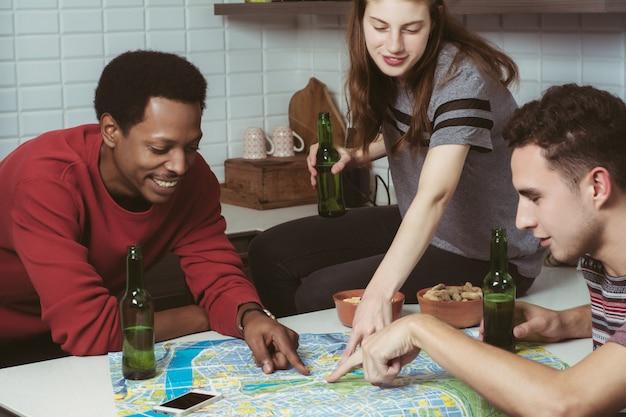 Três amigos planejando uma viagem em casa. Foto Premium