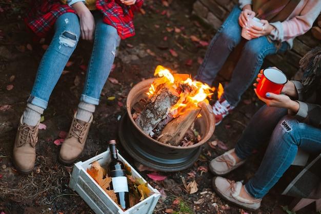 Três amigos relaxam confortavelmente e bebem vinho em uma noite de outono ao ar livre perto da lareira no quintal Foto Premium