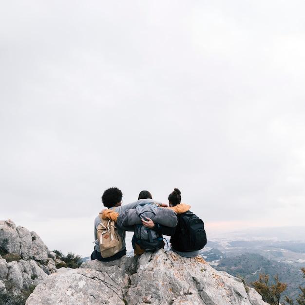 Três amigos sentados no topo da montanha, apreciando a vista Foto gratuita