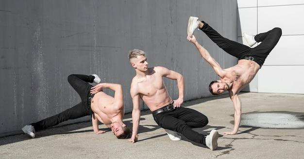 Três artistas dançando hip hop praticando fora Foto gratuita