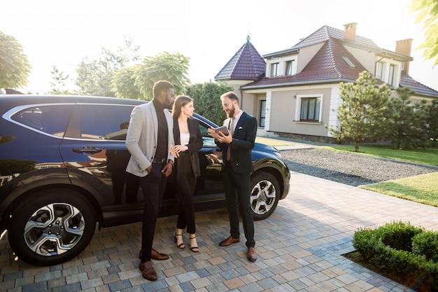 Três bem sucedidos empresários confiantes multiétnicas em roupas casuais inteligentes usando tablet perto de carro, em pé ao ar livre no quintal do moderno centro de negócios Foto Premium