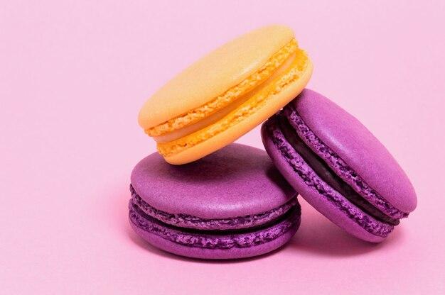Três bolinhos de amêndoa coloridos em um fundo cor-de-rosa. Foto Premium