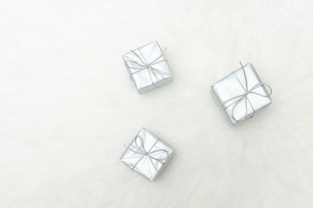 Três caixas de presente de prata sobre fundo branco Foto Premium