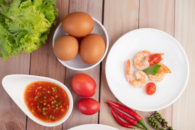 Três camarão fresco, ovos, pimentão, molho e meias tomates em um prato branco em um de madeira. Foto gratuita