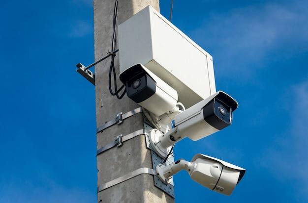 Três câmeras de cftv ao ar livre brancas no pilar de concreto na rua Foto Premium