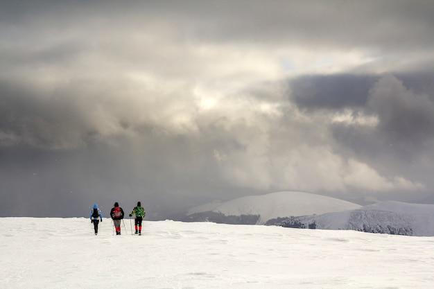 Três caminhantes em roupas brilhantes com mochilas no campo nevado, caminhando em direção a montanha distante Foto Premium