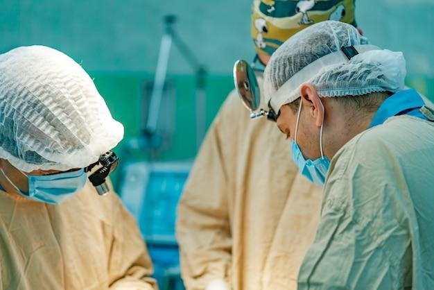 Três cirurgiões em vestidos médicos brancos e em máscaras executam a operação do paciente. Foto Premium