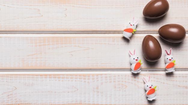 Três coelhos brancos de páscoa e ovos de chocolate na mesa de madeira Foto gratuita