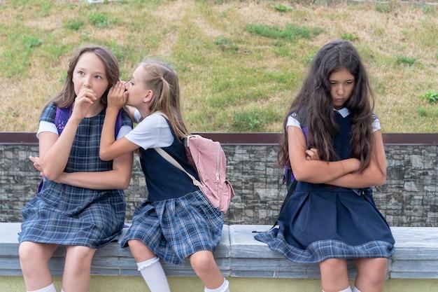 Três colegiais estão sentadas no pátio da escola Foto Premium