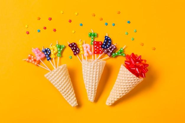 Três cones de waffle no laço da fita; velas de texto feliz aniversário com granulado em pano de fundo amarelo Foto gratuita