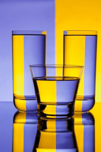 Três copos com água sobre a parede roxa e amarela Foto gratuita