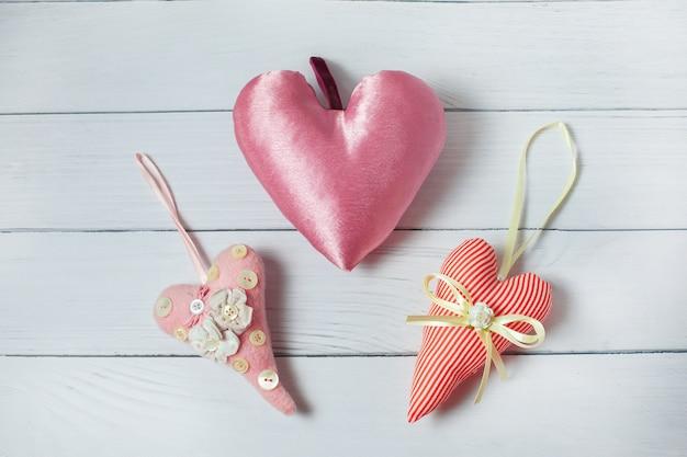 Três corações cor-de-rosa de matéria têxtil no fundo de madeira. decoração de dia dos namorados de estilo vintage Foto Premium