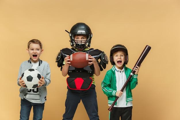 Três crianças felizes mostram trajes diferentes do esporte Foto gratuita