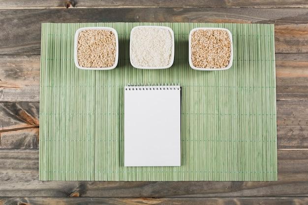 Três, diferente, tipo, de, cru, arroz, bacias, com, espiral, notepad, ligado, verde, placemat, sobre, a, tabela Foto gratuita