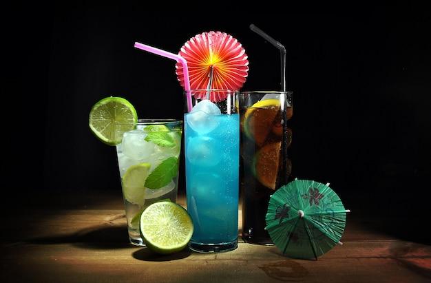 Três diferentes, cocktails refrescantes na mesa de madeira Foto Premium