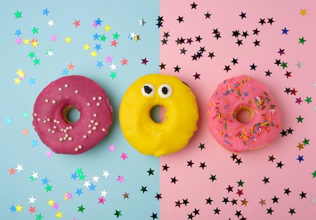 Três donuts redondos em um fundo colorido, banana e com bagas Foto Premium