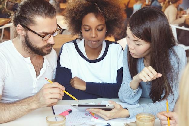 Três empresários ambiciosos desenvolvendo a estratégia de negócios de seu start-up. Foto gratuita