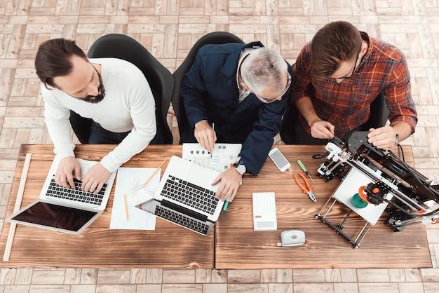 Três, engenheiros, sentar-se tabela, com, laptop Foto Premium