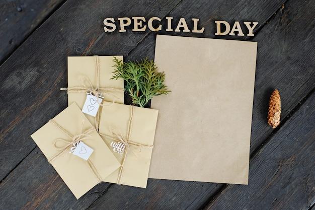 Três envelopes artesanais e um pedaço de papel artesanal. lugar para o seu texto e mensagem. embrulho de presente artesanal. Foto Premium