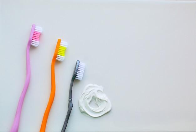 Três escovas de dentes em um fundo branco e creme dental branco Foto Premium