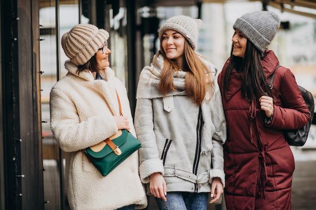 Três estudantes com roupa de inverno na rua Foto gratuita