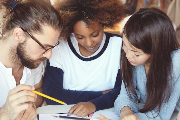 Três estudantes universitários trabalhando em casa, sentados no refeitório, fazendo pesquisas, procurando informações necessárias na internet, usando tablet digital. Foto gratuita
