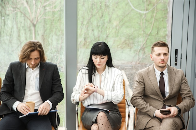 Três funcionários de escritório estão esperando por um compromisso Foto Premium