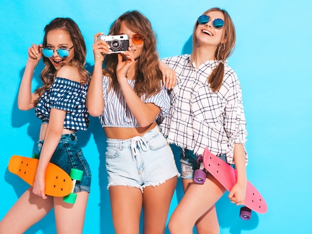 Três garotas sorridentes elegantes sexy bonitas com skates centavo coloridos. mulheres em roupas de camisa quadriculada verão posando. modelos tirando fotos na câmera fotográfica retrô Foto gratuita