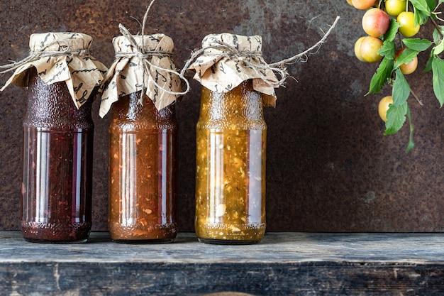 Três garrafas de vidro de molho tkemali georgiano sortido com ingredientes na mesa de madeira rústica. Foto gratuita
