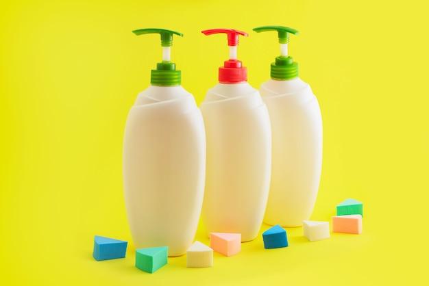 Três garrafas plásticas com o distribuidor no fundo amarelo. Foto Premium