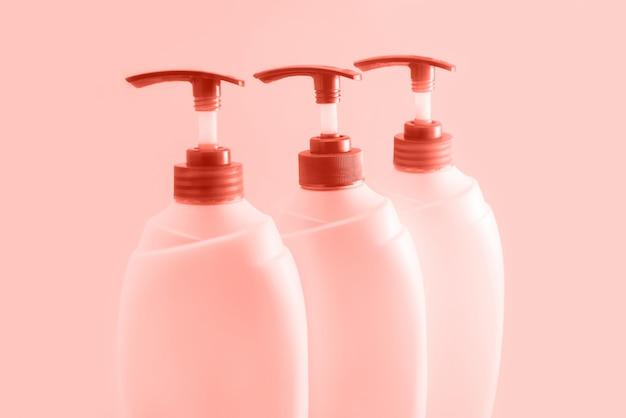 Três garrafas plásticas com o distribuidor no fundo coral. Foto Premium