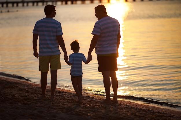 Três gerações masculinas pelo mar ao pôr do sol Foto Premium