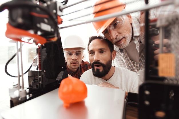 Três homens estão trabalhando para preparar modelo impresso Foto Premium